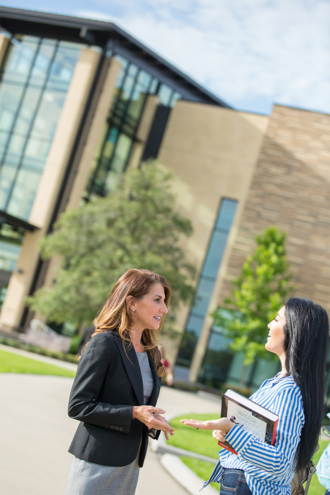 Two women talking outside of campus building