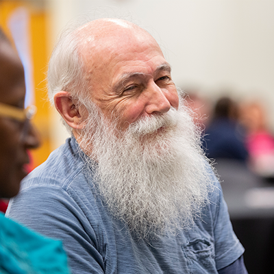 Male with white beard attending a Peace Week meeting
